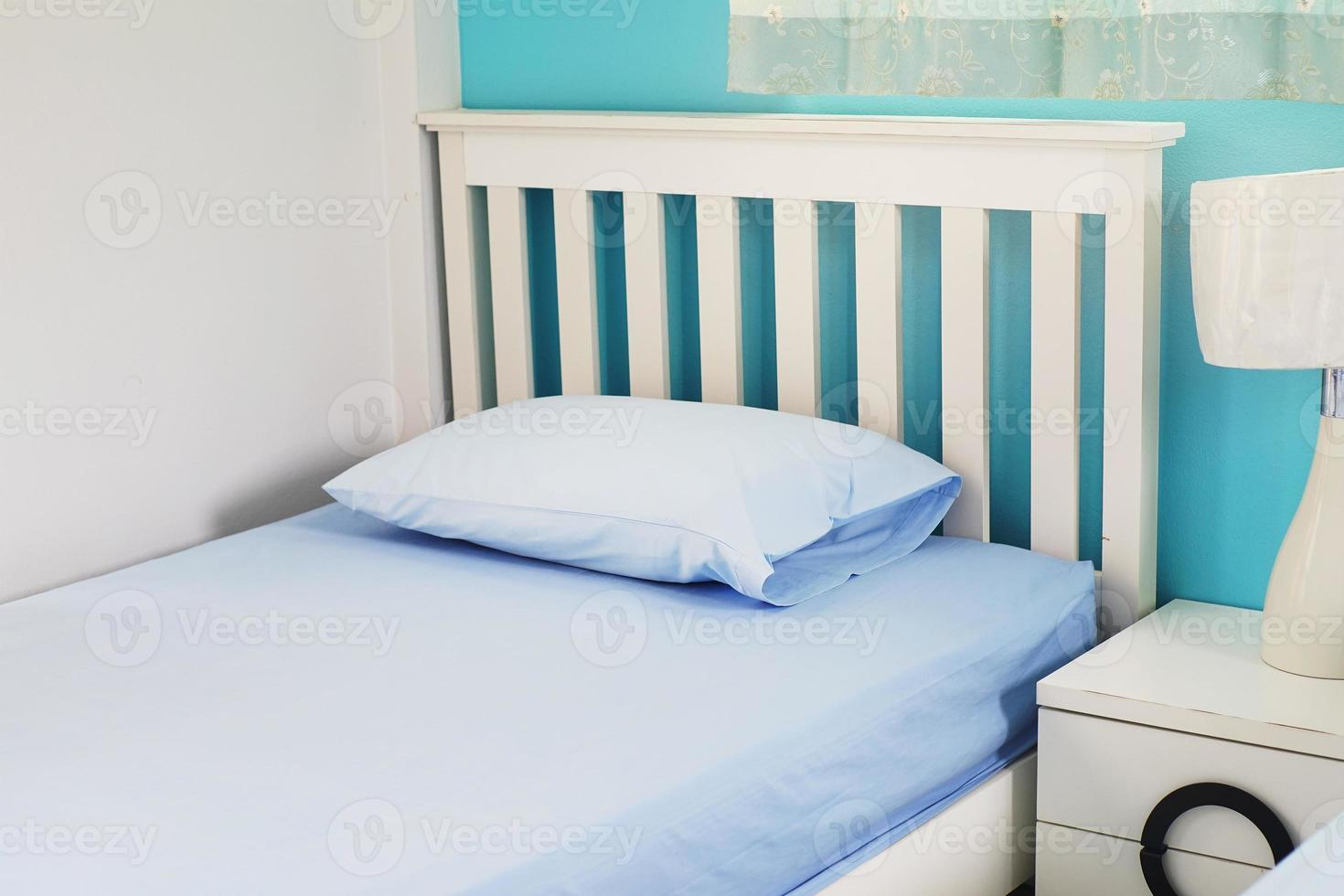 light blue pillow on white  bed in bedroom photo