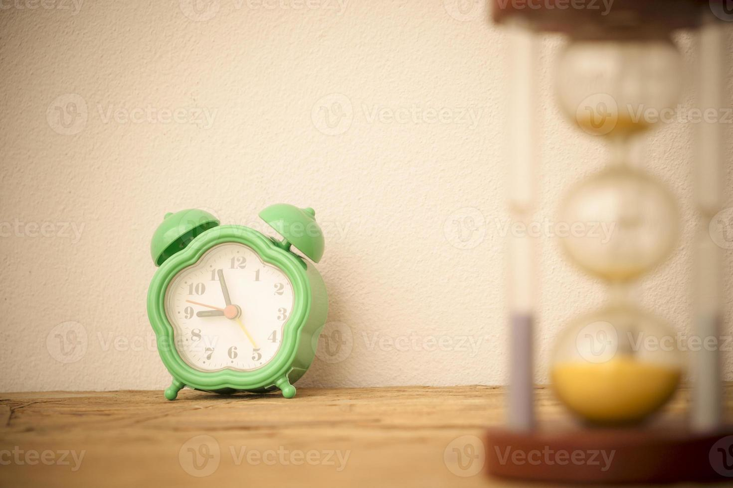 Green Clock and hourglass on wooden table photo