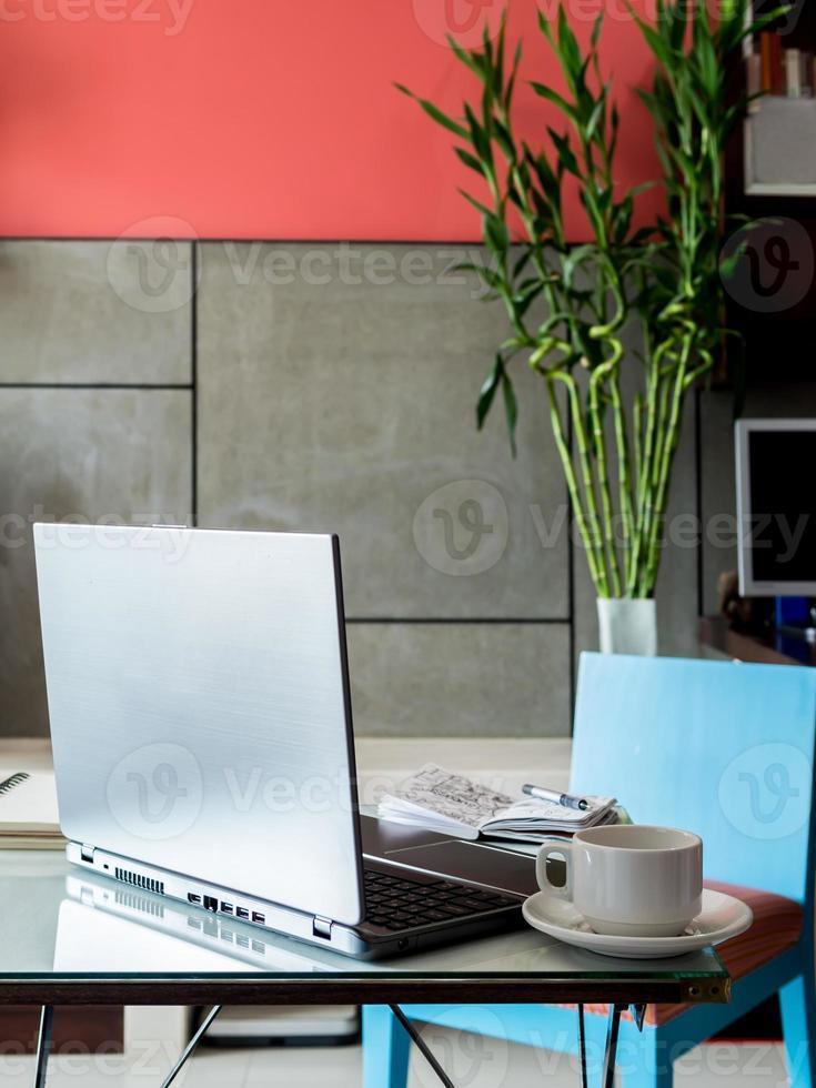Lugar de trabajo moderno con computadora portátil y taza de café en el escritorio foto