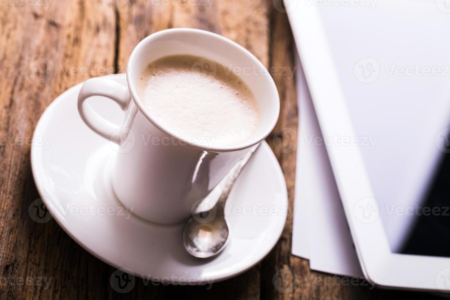 tableta digital y café sobre fondo de madera vieja foto
