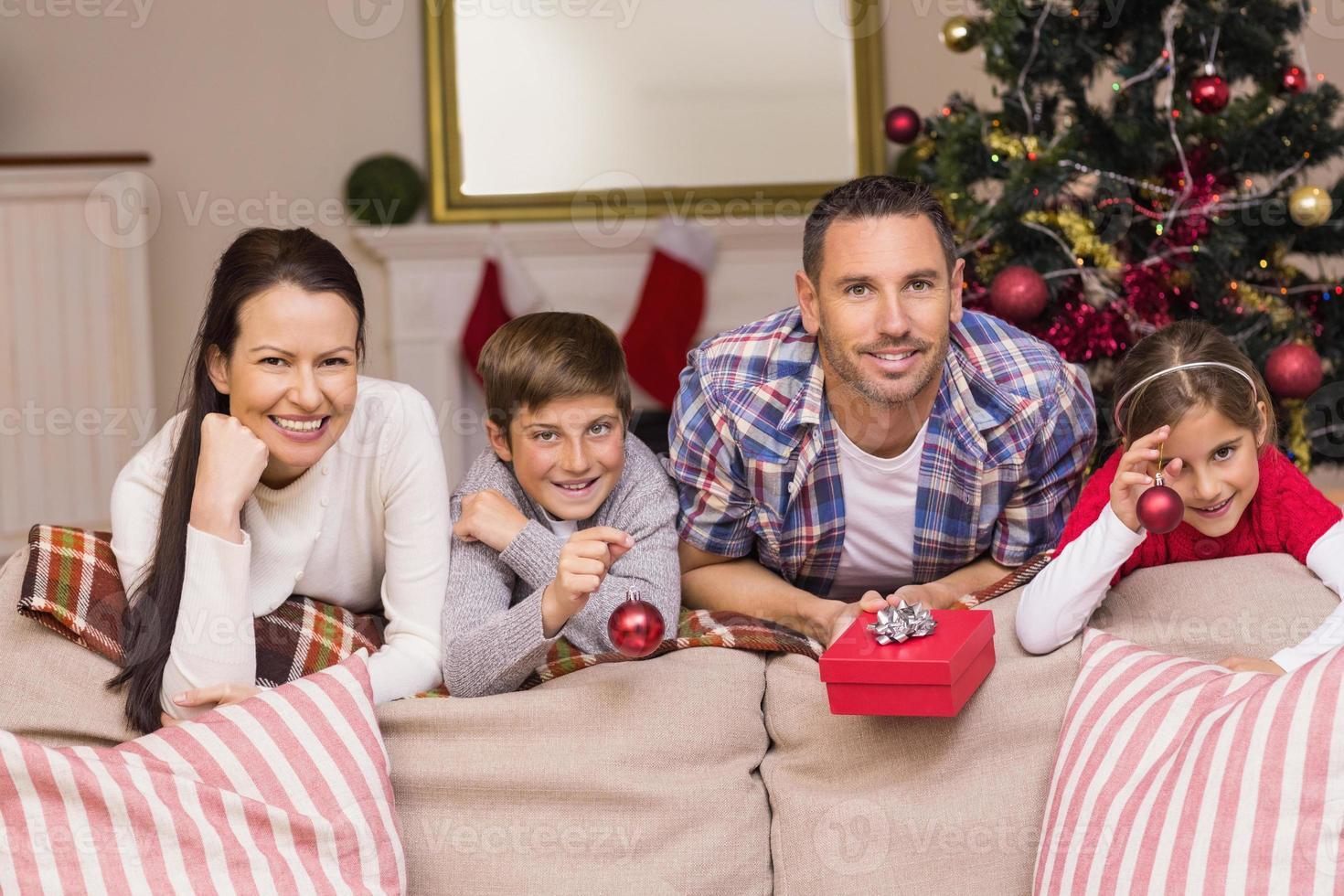 familia feliz recostada en el sofá foto