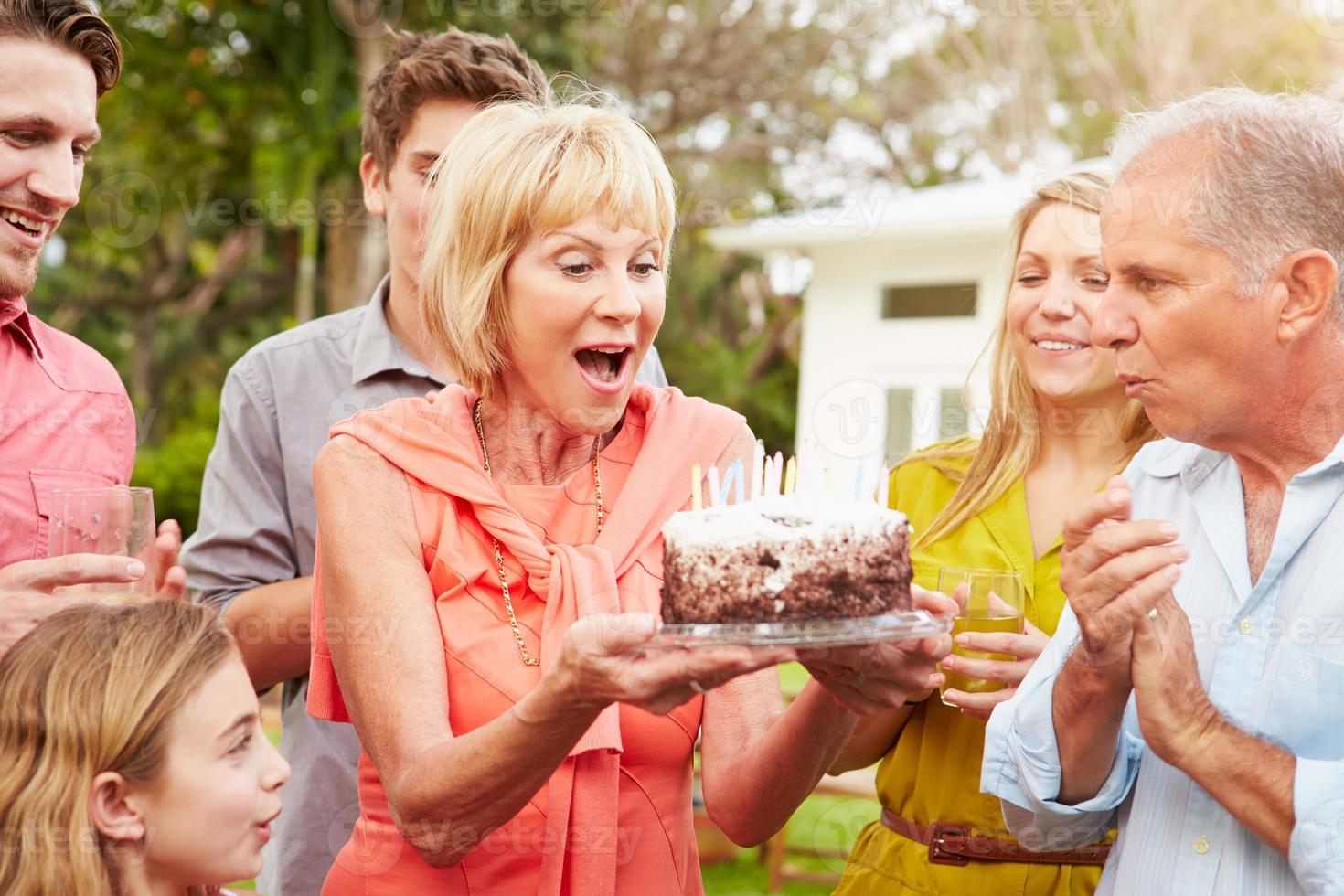 Familia multigeneración celebrando cumpleaños en jardín foto