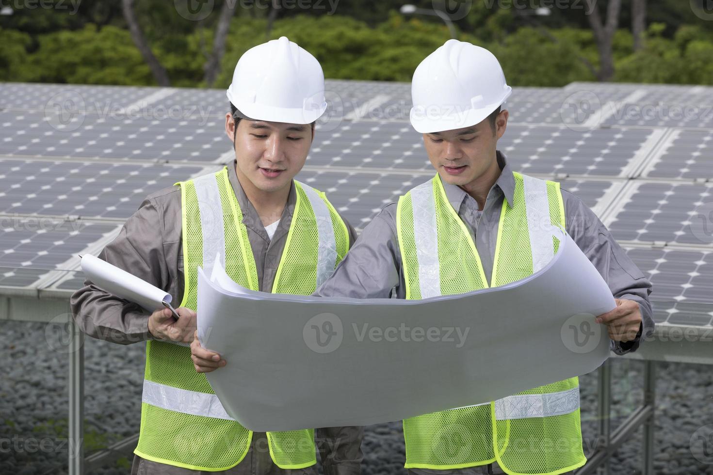 dos ingenieros asiáticos de paneles solares en el trabajo. foto