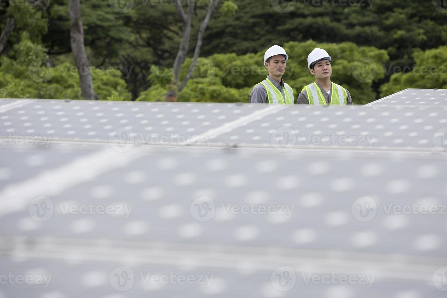 Two Asian engineers in a solar panel station photo
