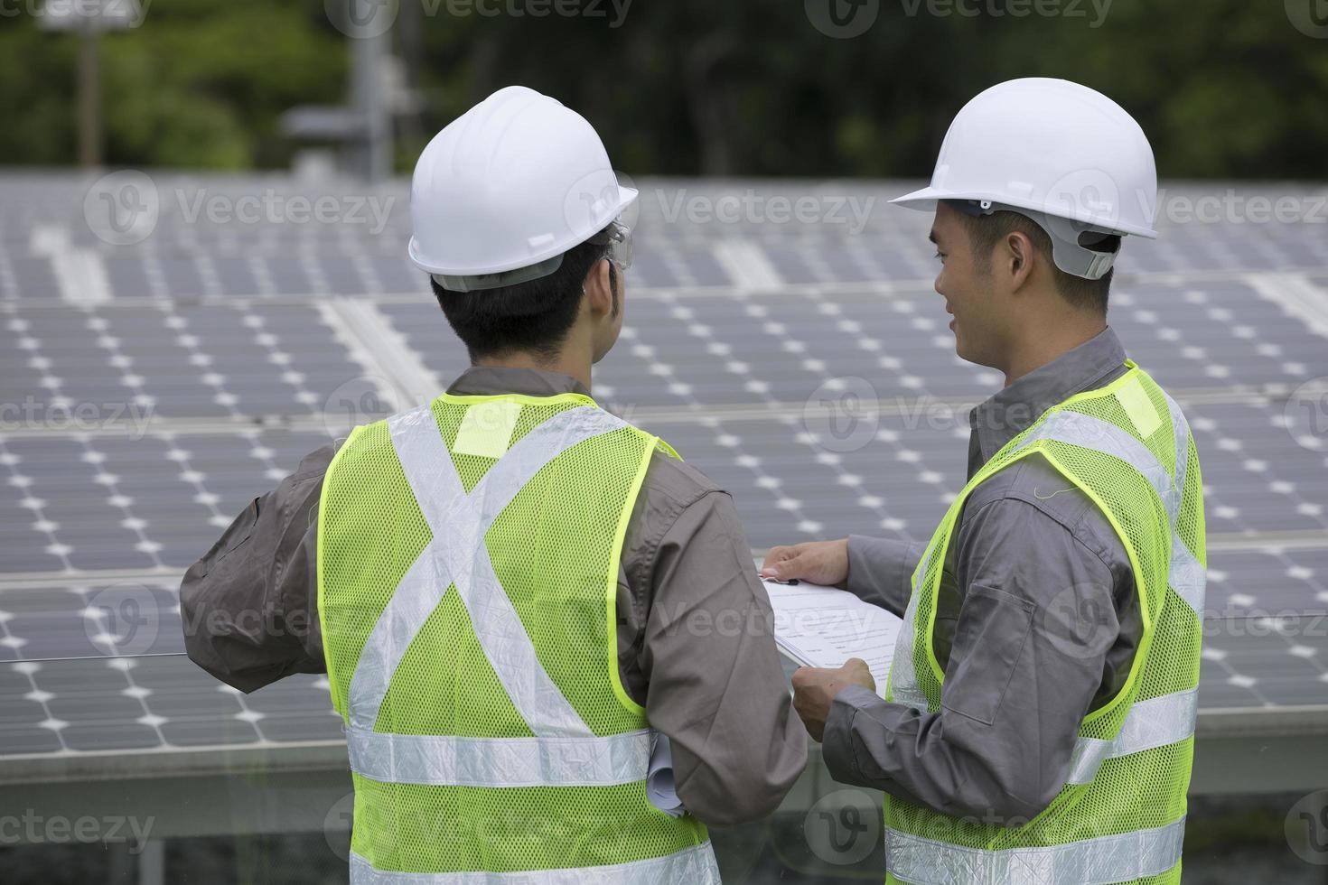dos ingenieros asiáticos en una estación de paneles solares foto