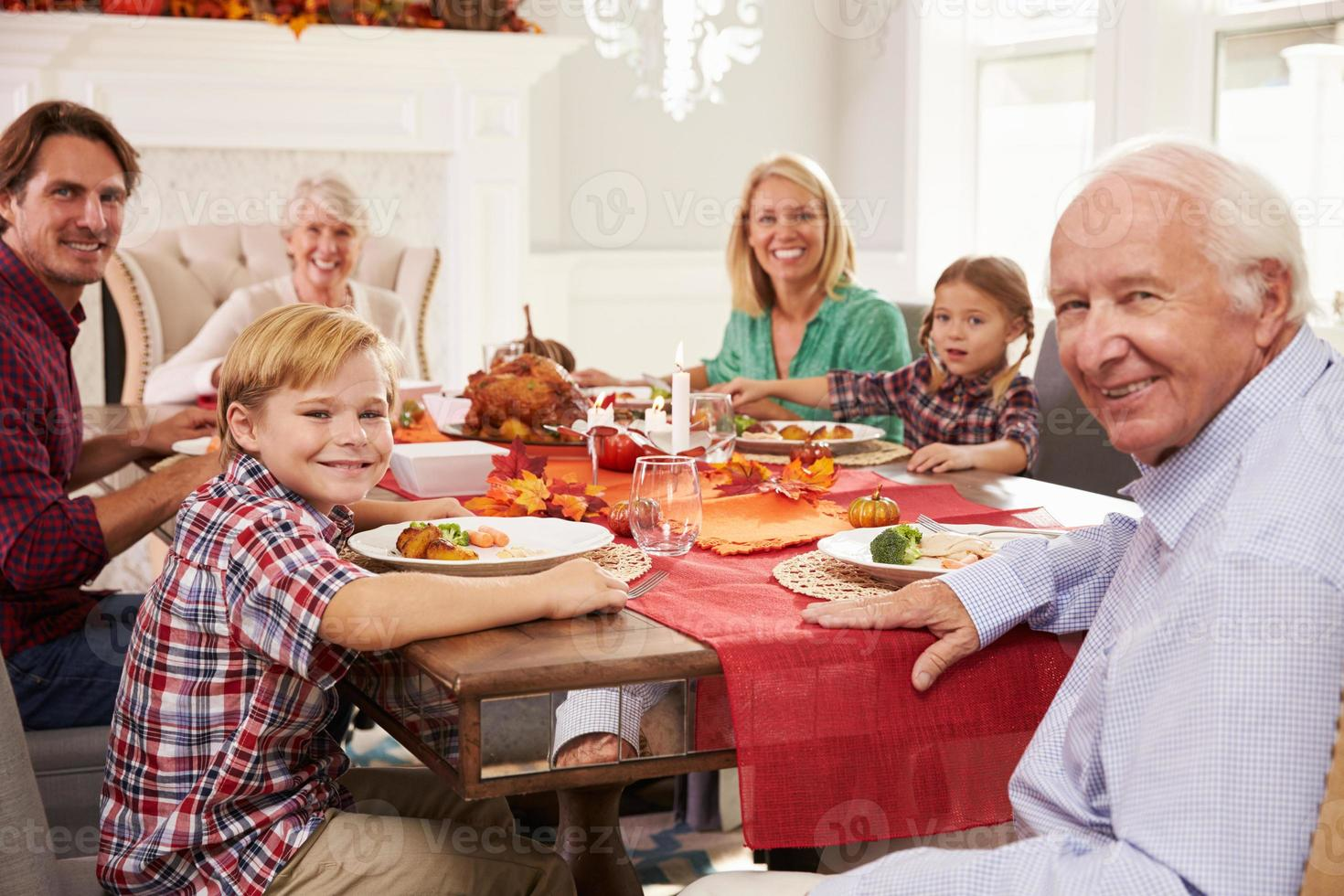 Family With Grandparents Enjoying Thanksgiving Meal At Table photo
