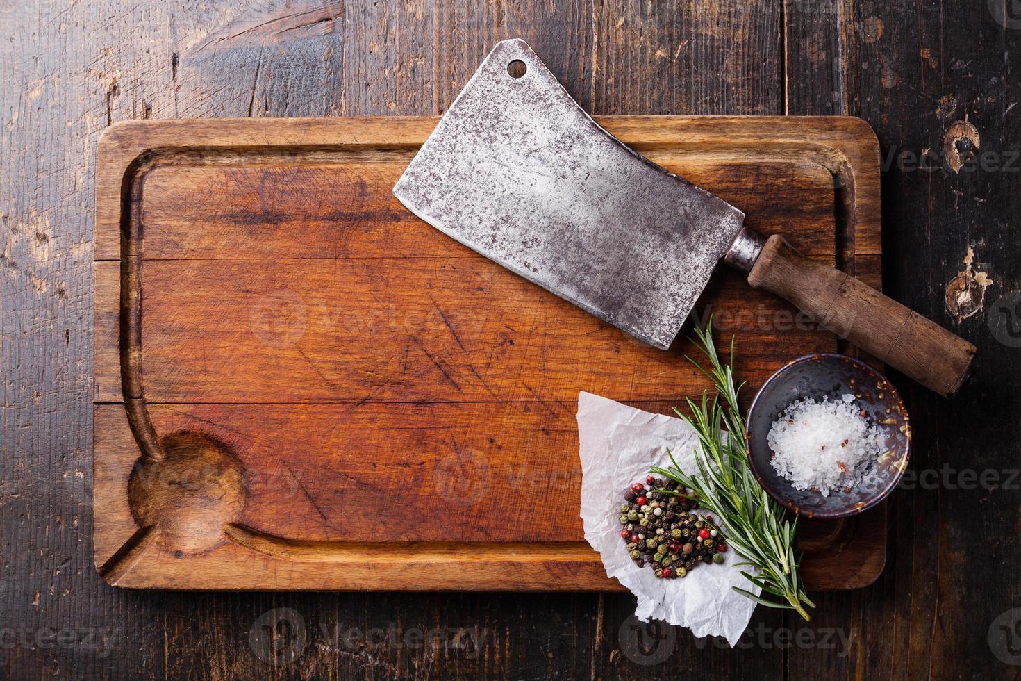 Tabla de cortar, condimentos y cuchilla de carne sobre fondo de madera oscura. foto