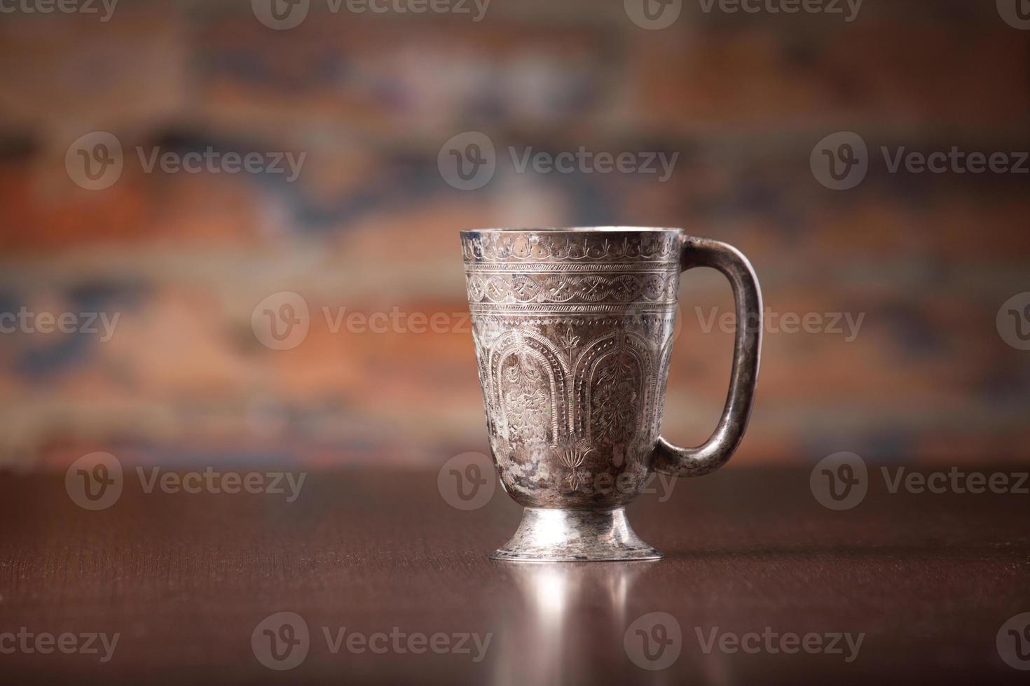 taza de café de metal con decoración árabe en escritorio de madera foto