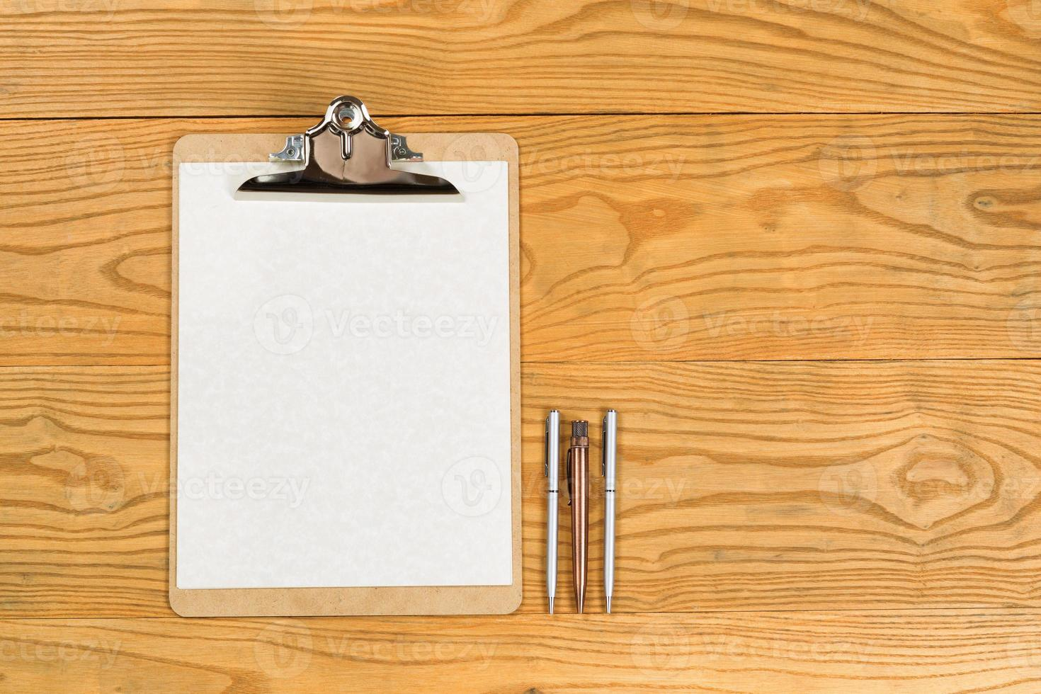 Blank clipboard with paper and pens on desktop photo