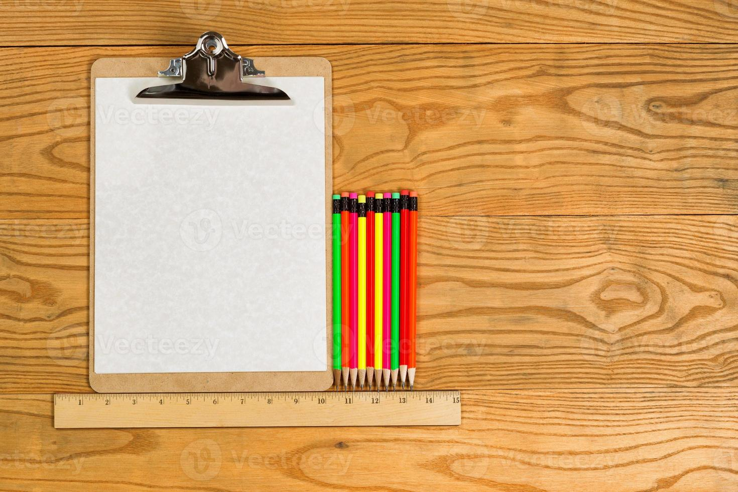 Blank clipboard with paper and colorful pencils on desktop photo