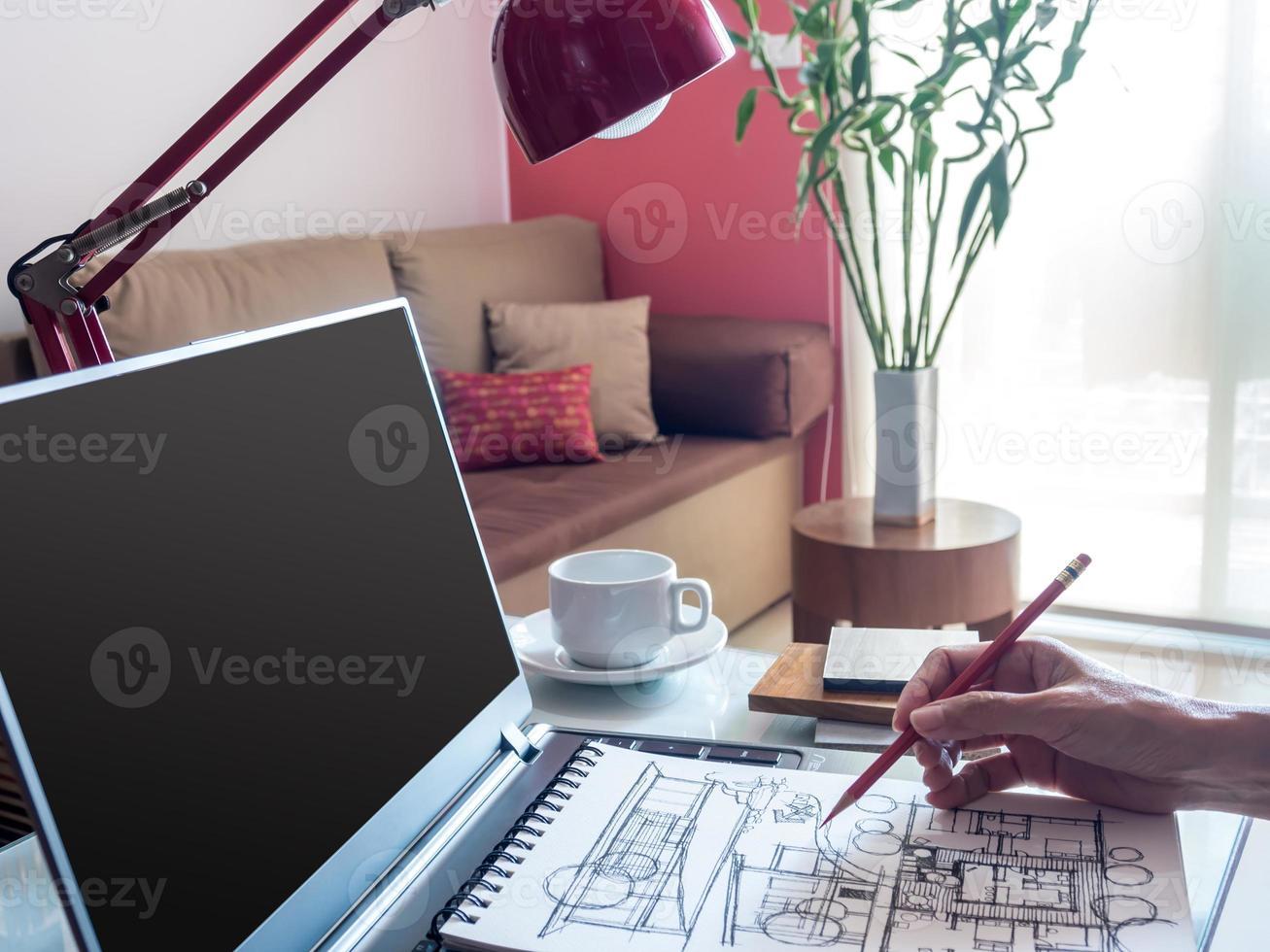 Diseñador trabajando con laptop y dibujo arquitectónico en un espacio de trabajo moderno foto