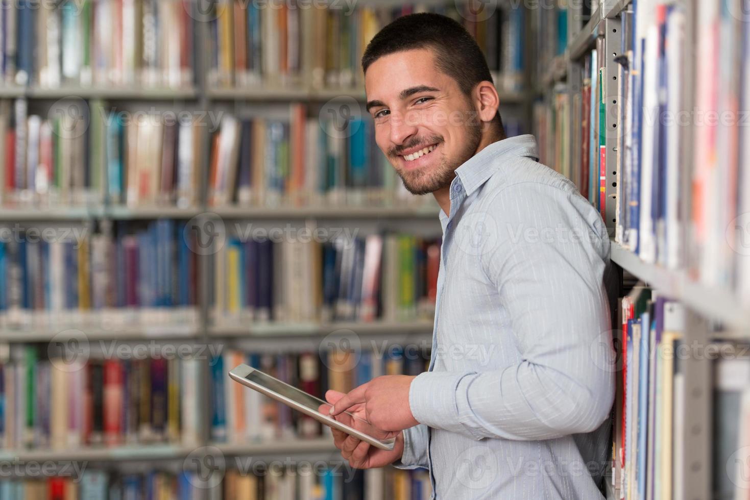 joven estudiante usando su computadora portátil en una biblioteca foto