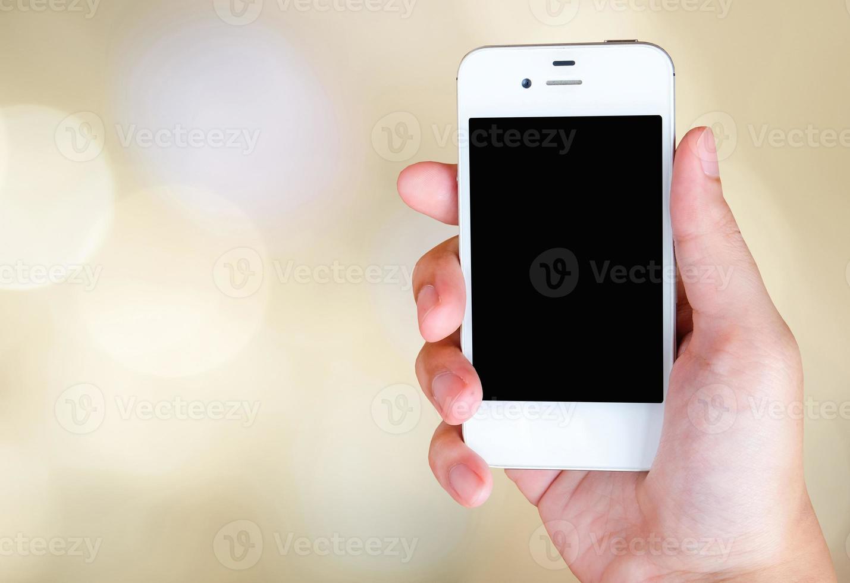 Teléfono inteligente en mano sobre fondo bokeh foto