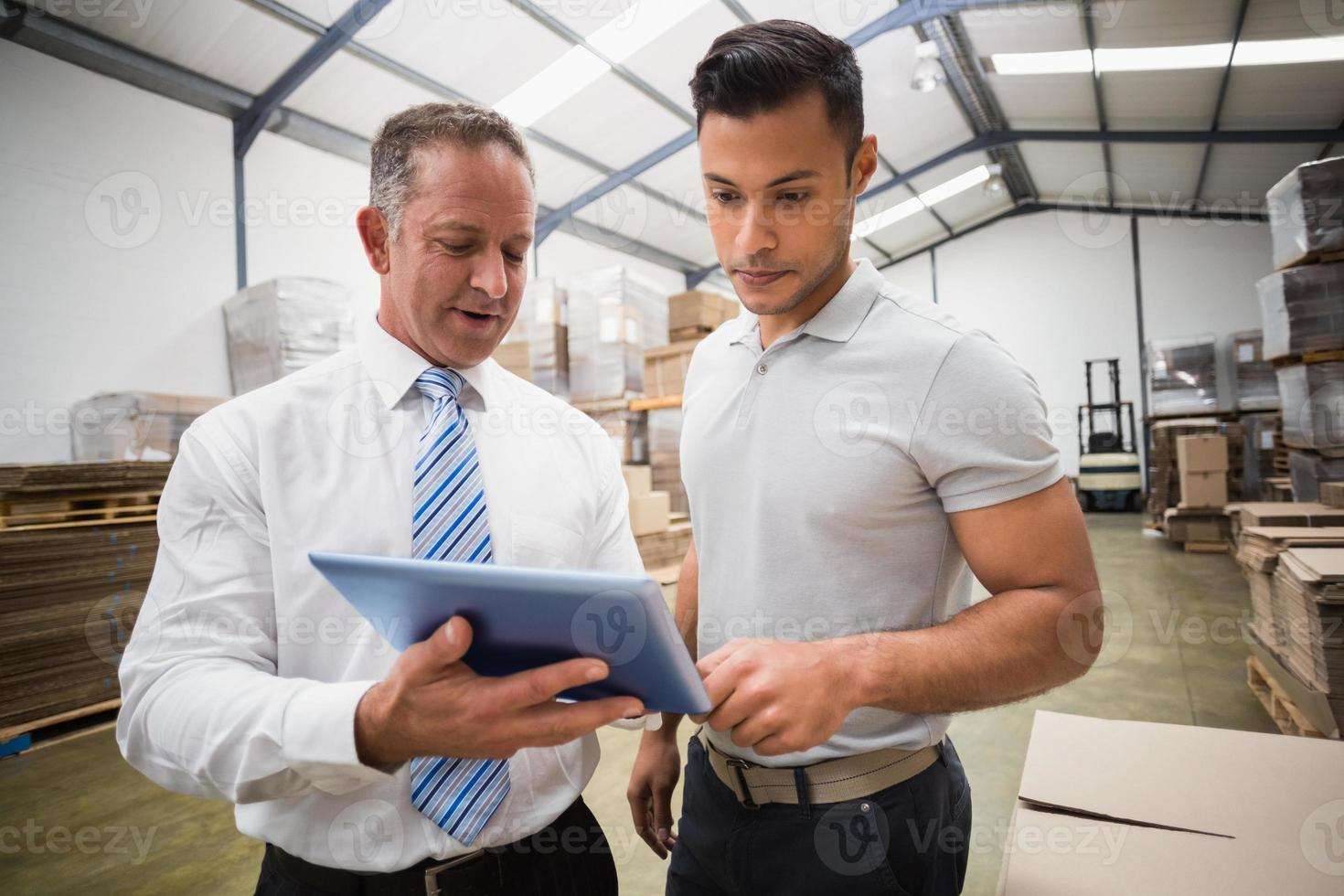 Warehouse manager using tablet pc with colleague photo
