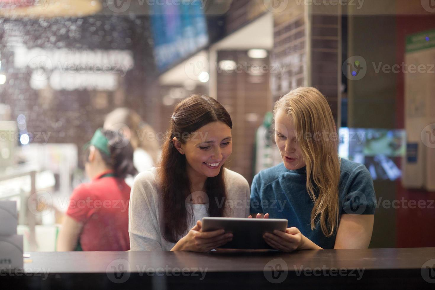 dos mujeres hablan alegremente en el restaurante usando tableta electrónica foto