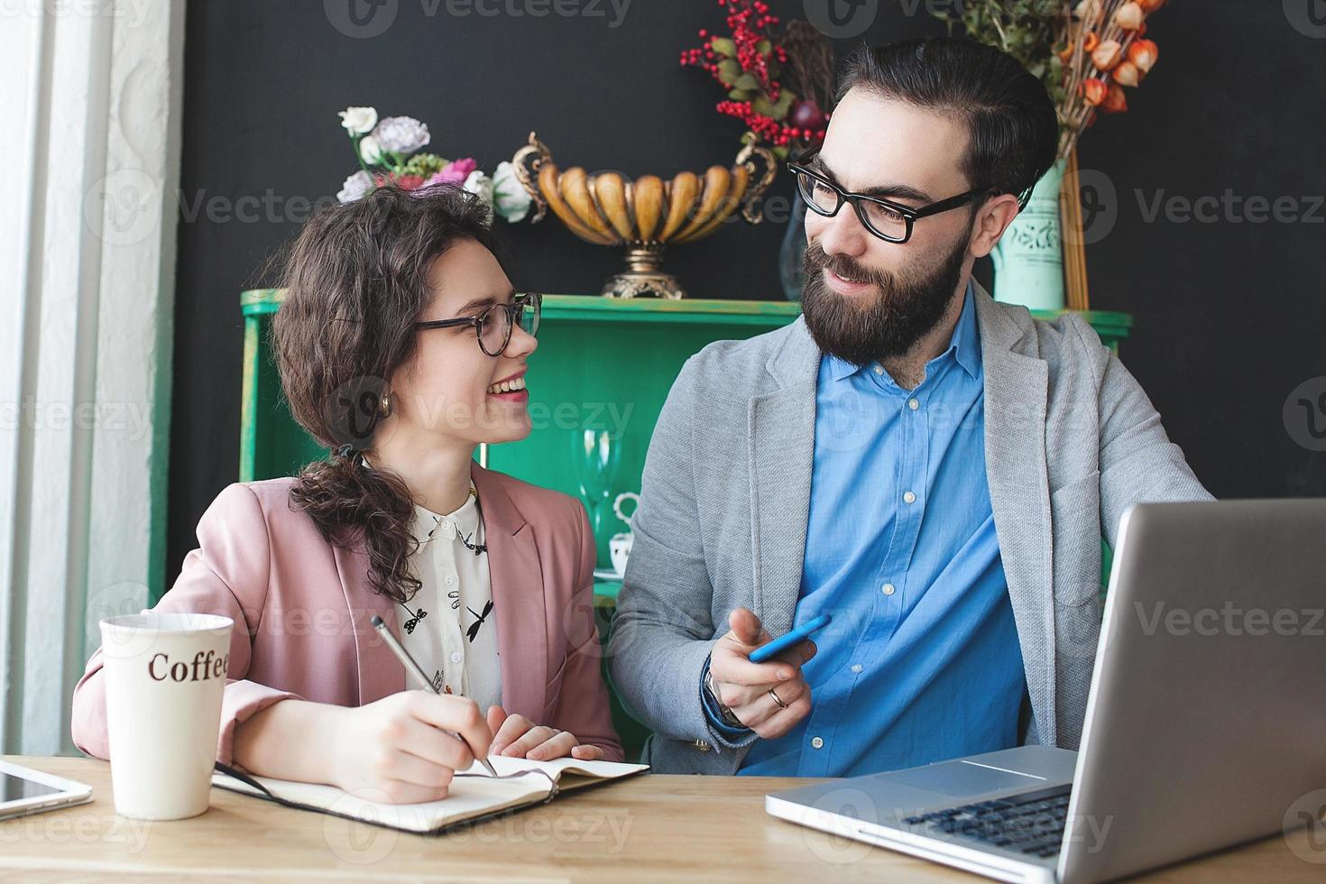 Modern team working in cafe with laptop, smartphone with coffee photo
