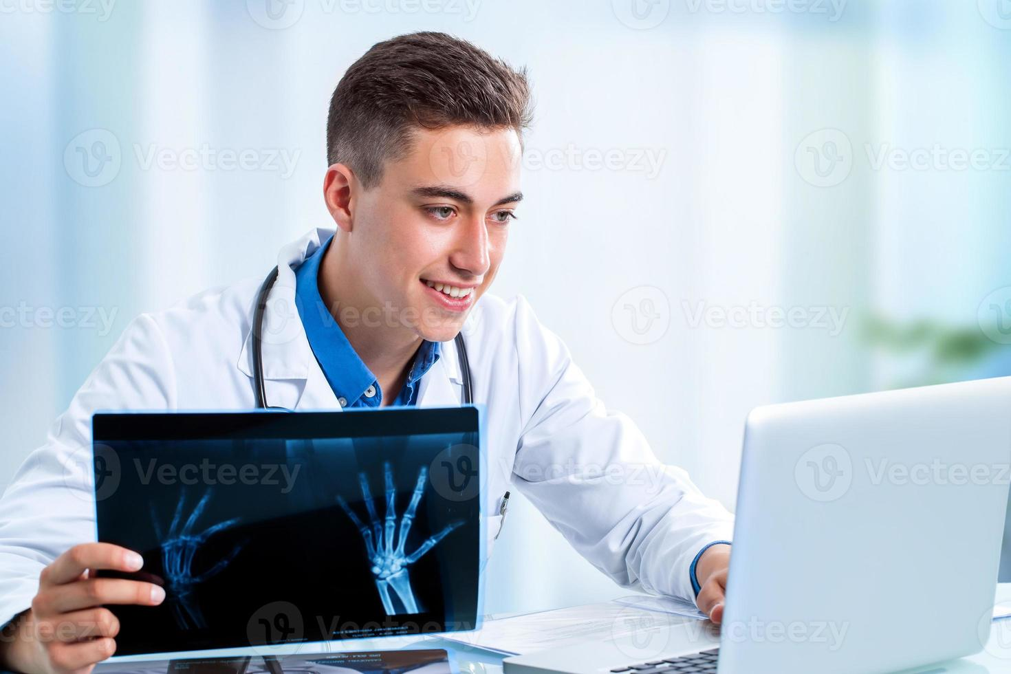 Handsome young doctor reviewing results on laptop. photo