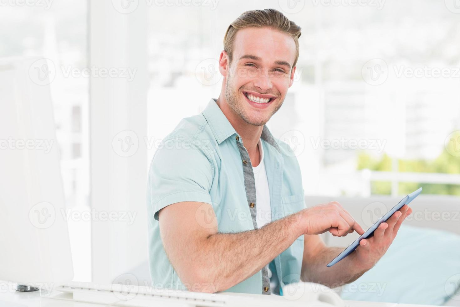 Happy casual businessman using tablet photo