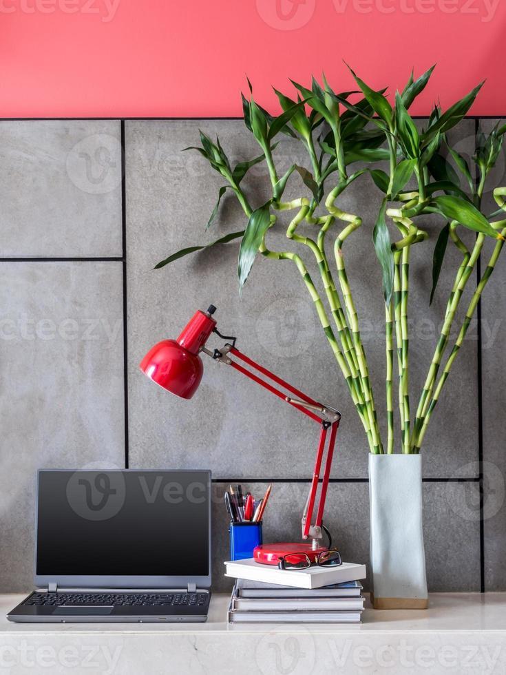 moderno escritorio de oficina con laptop, lámpara y jarrón con flores foto