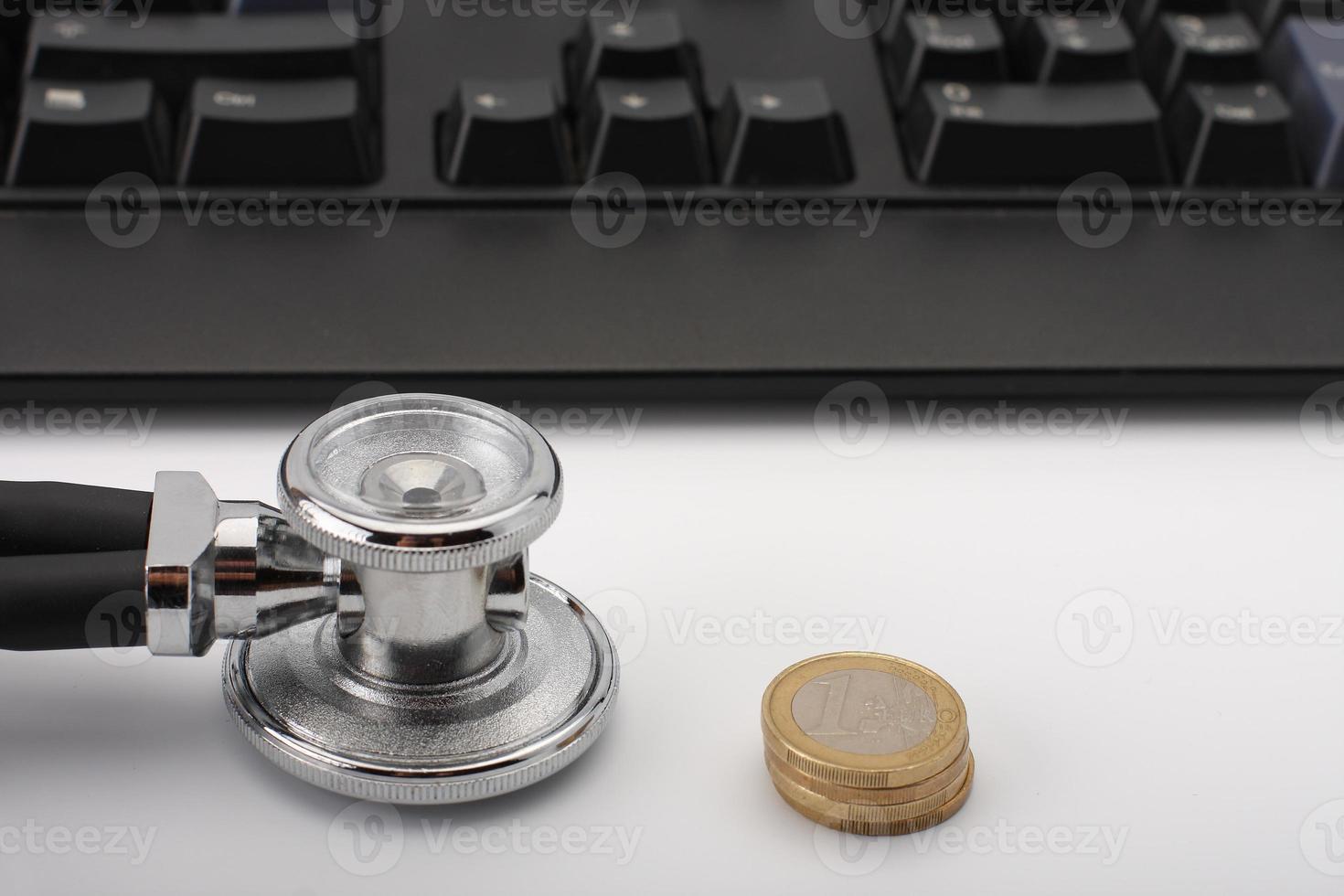 Estetoscopio, dinero, teclado en blanco, concepto médico. foto