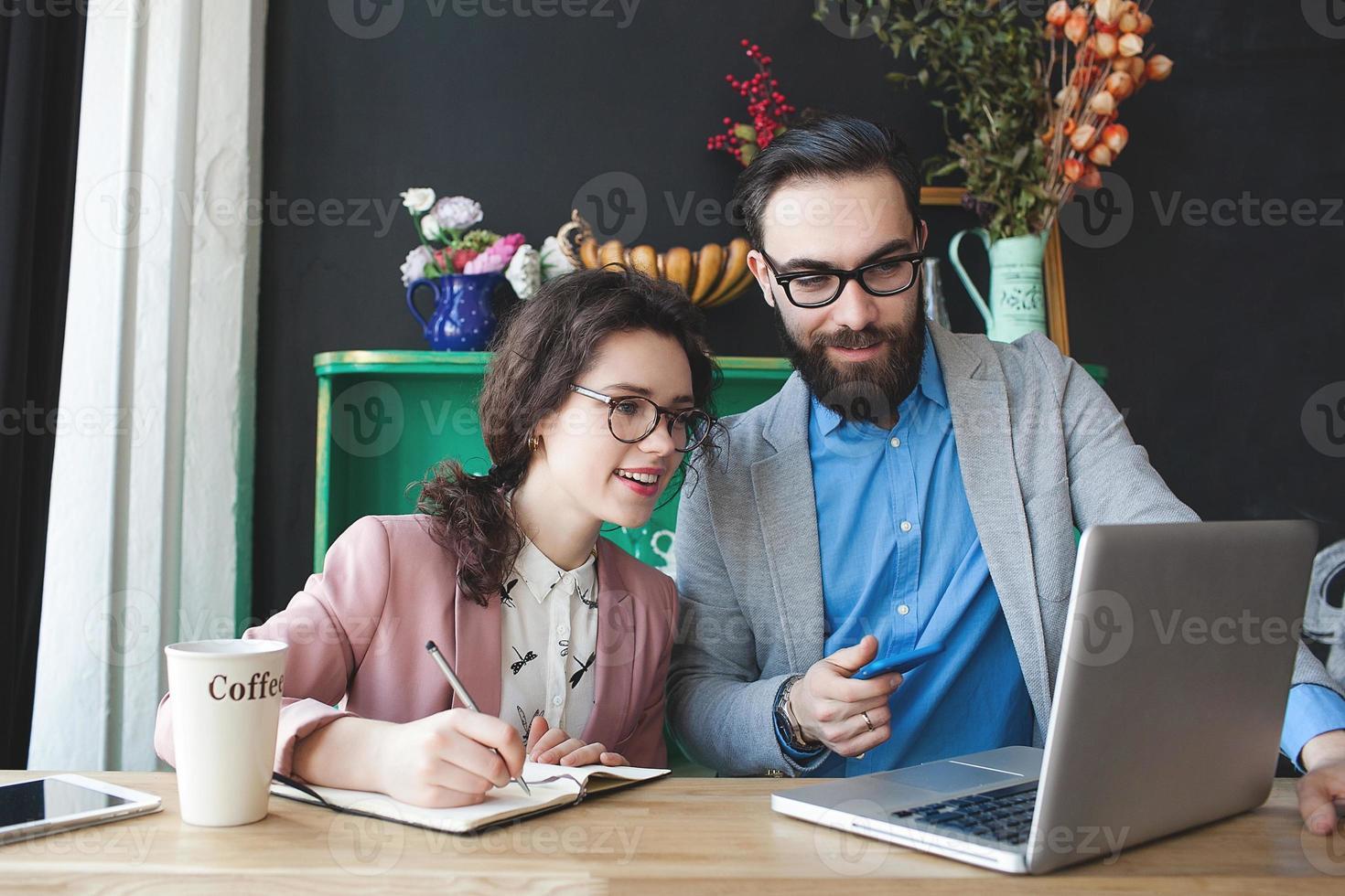Equipo moderno trabajando en café con laptop, smartphone con café. foto