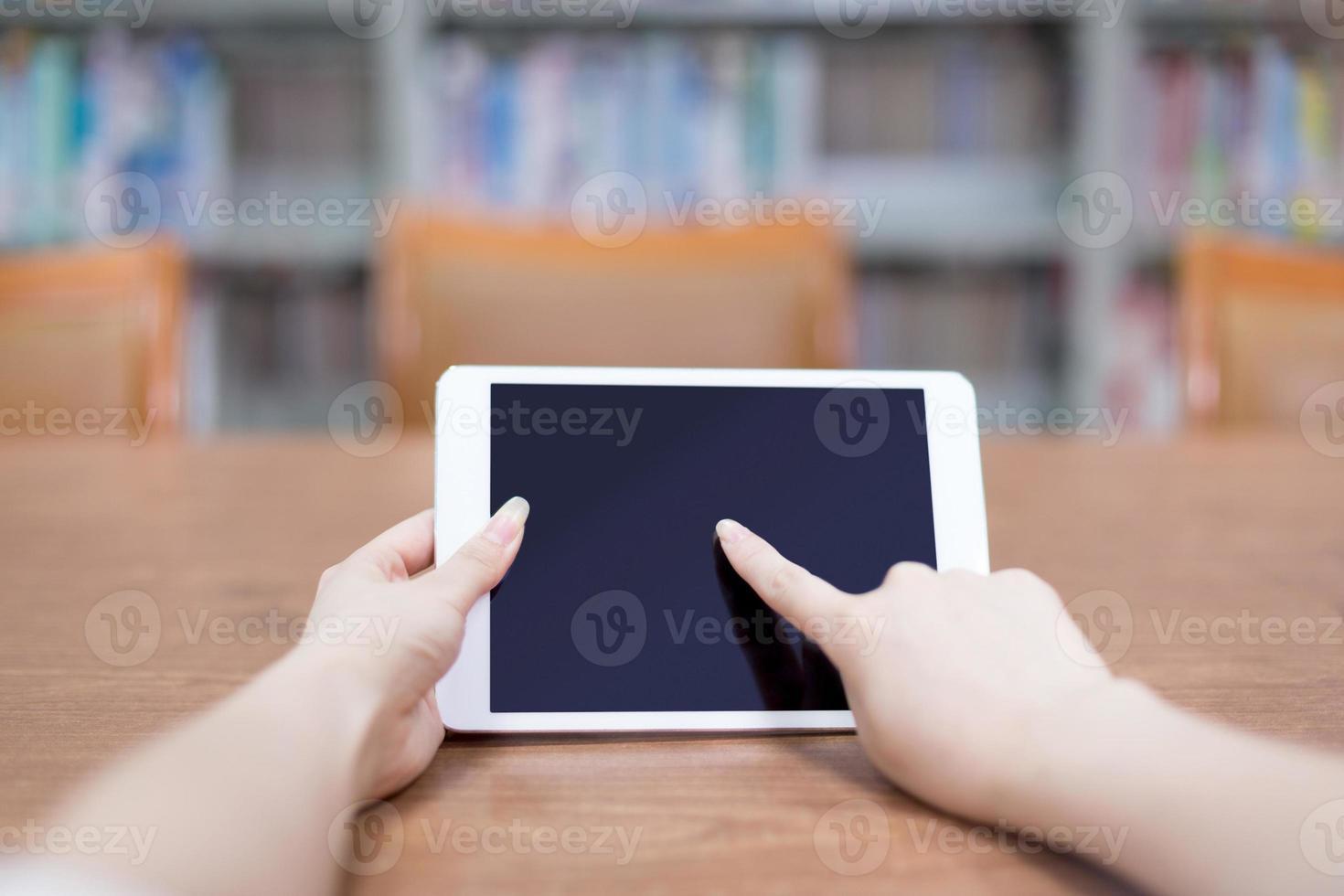 mano tocando la tableta en la biblioteca foto