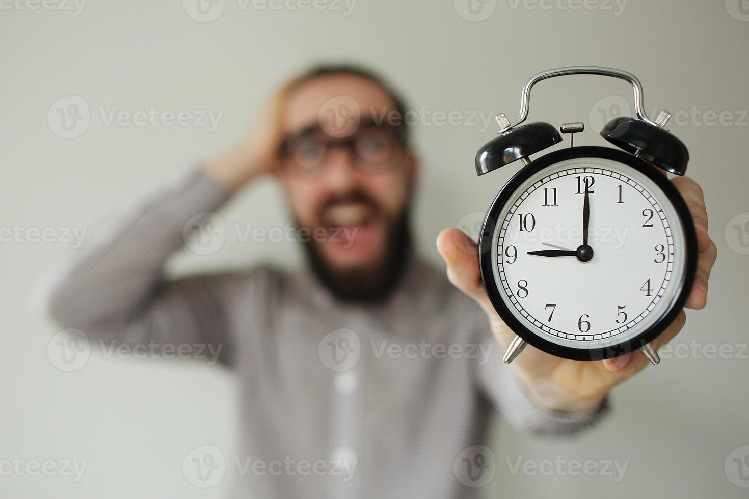 Panic man holds alarm clock and head scared of deadline photo