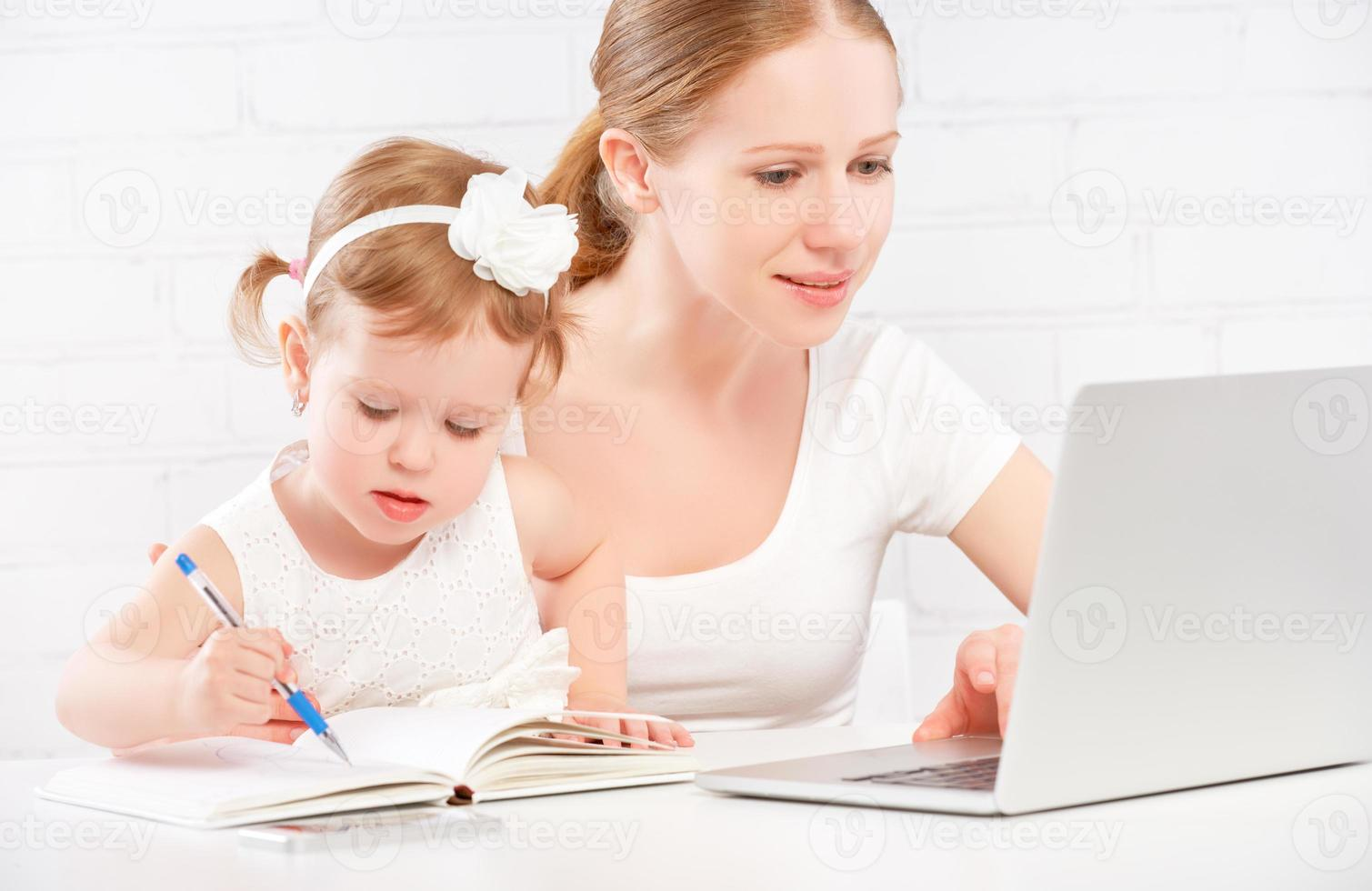 family mother and child baby at home working on computer photo
