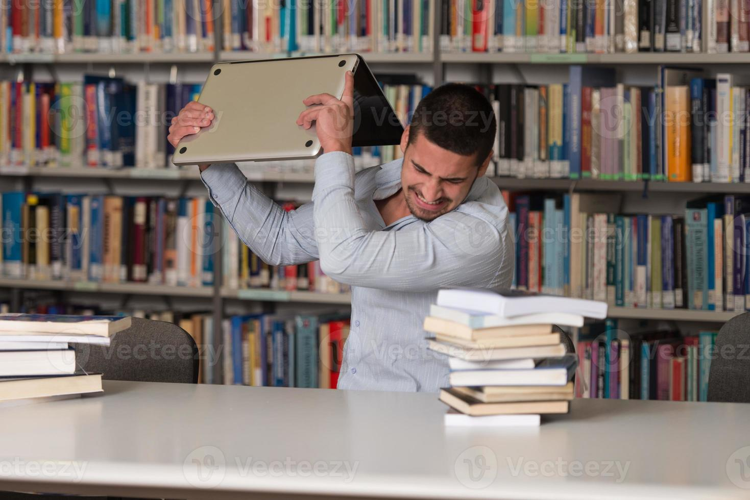 estudiante furioso tirando su computadora portátil foto
