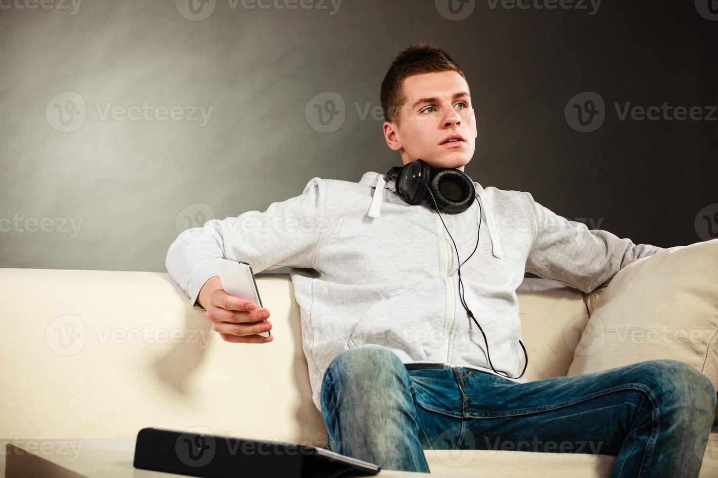Guy with tablet headphones phone on couch photo