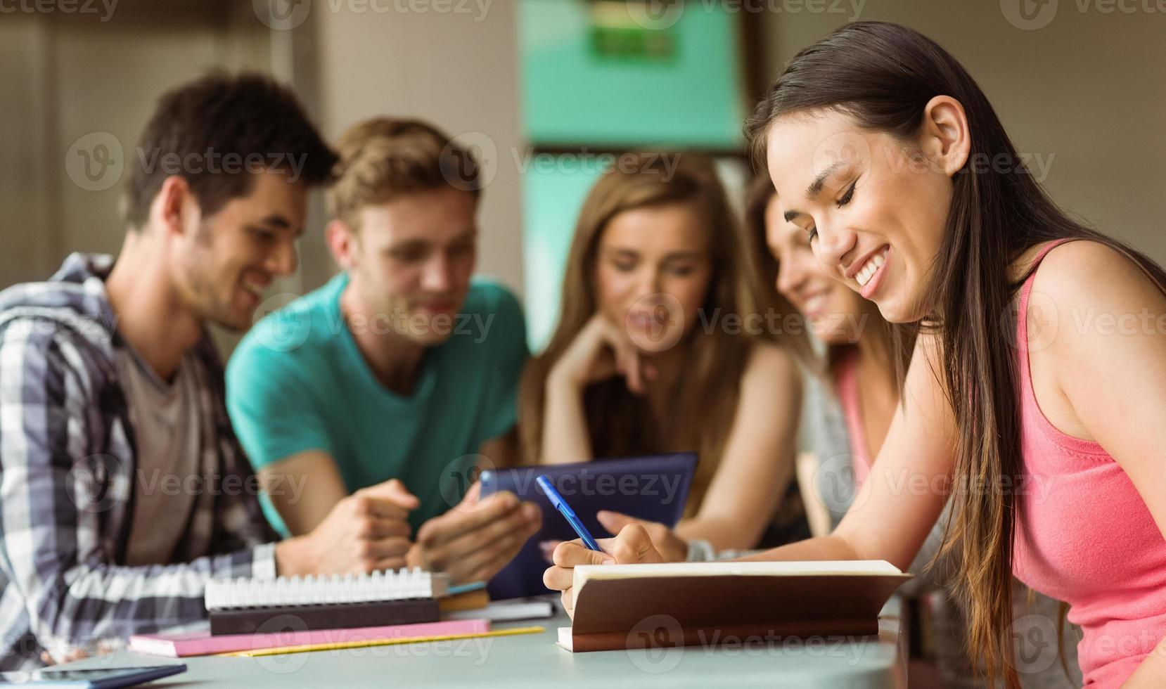 amigos sonrientes sentados estudiando y usando tablet pc foto