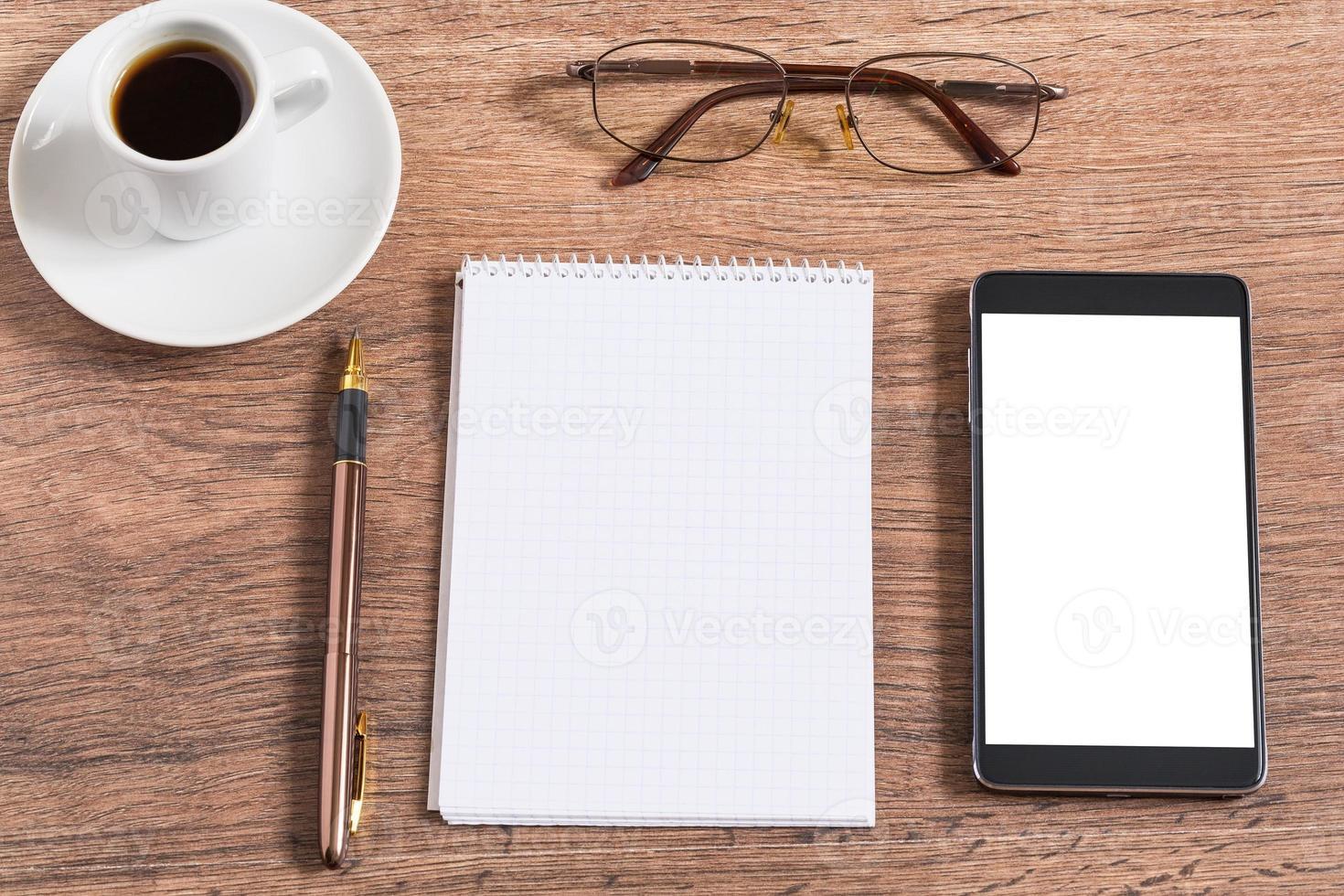cuaderno con bolígrafo, teléfono inteligente y taza de café foto