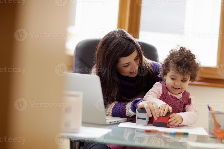 madre jugando con hija mientras realiza múltiples tareas foto