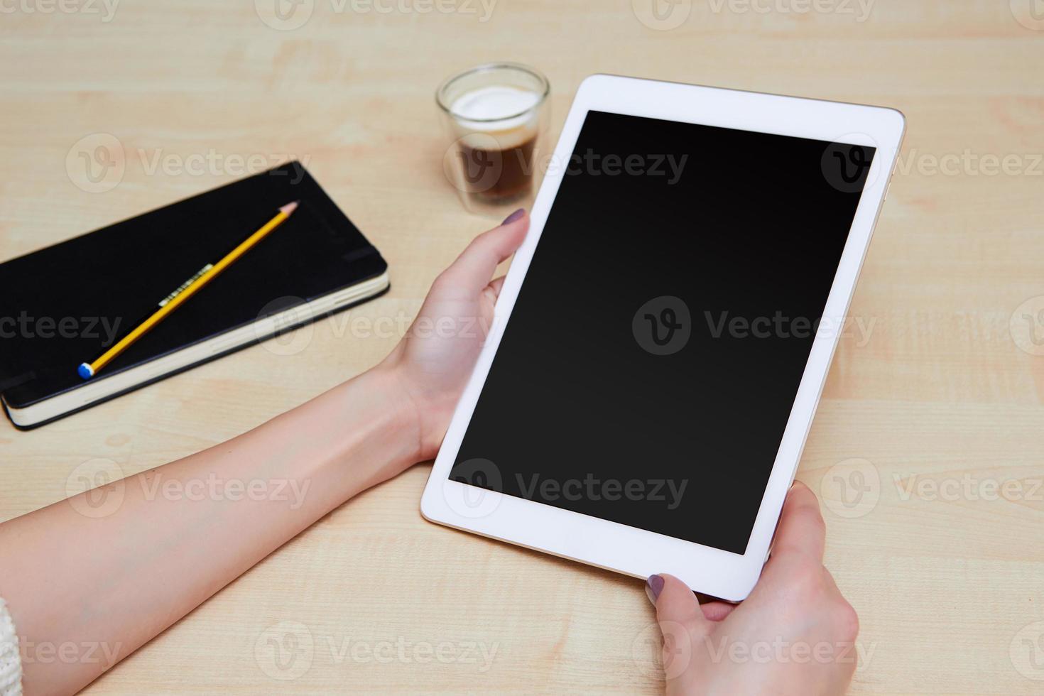 Persona sosteniendo una tableta blanca digital con pantalla en blanco foto