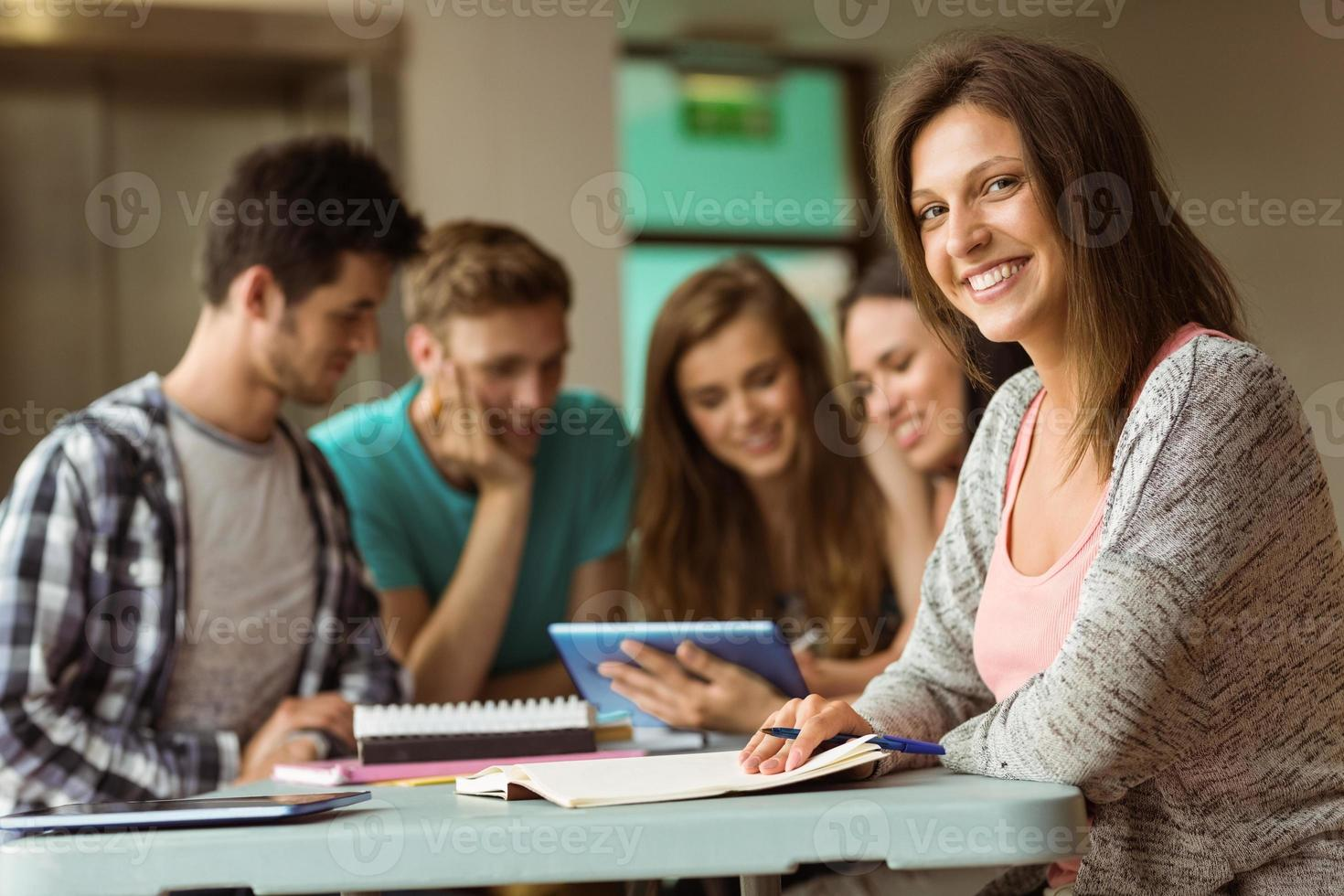 Smiling friends sitting studying and using tablet pc photo
