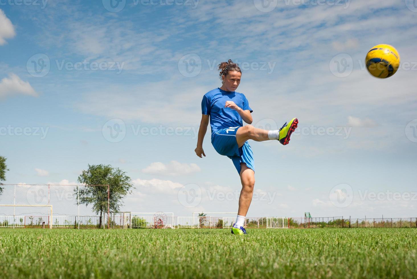 niña pateando el balón de fútbol foto