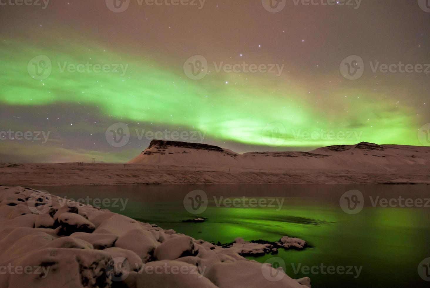 Aurora Borealis curls above mountains and sea. photo