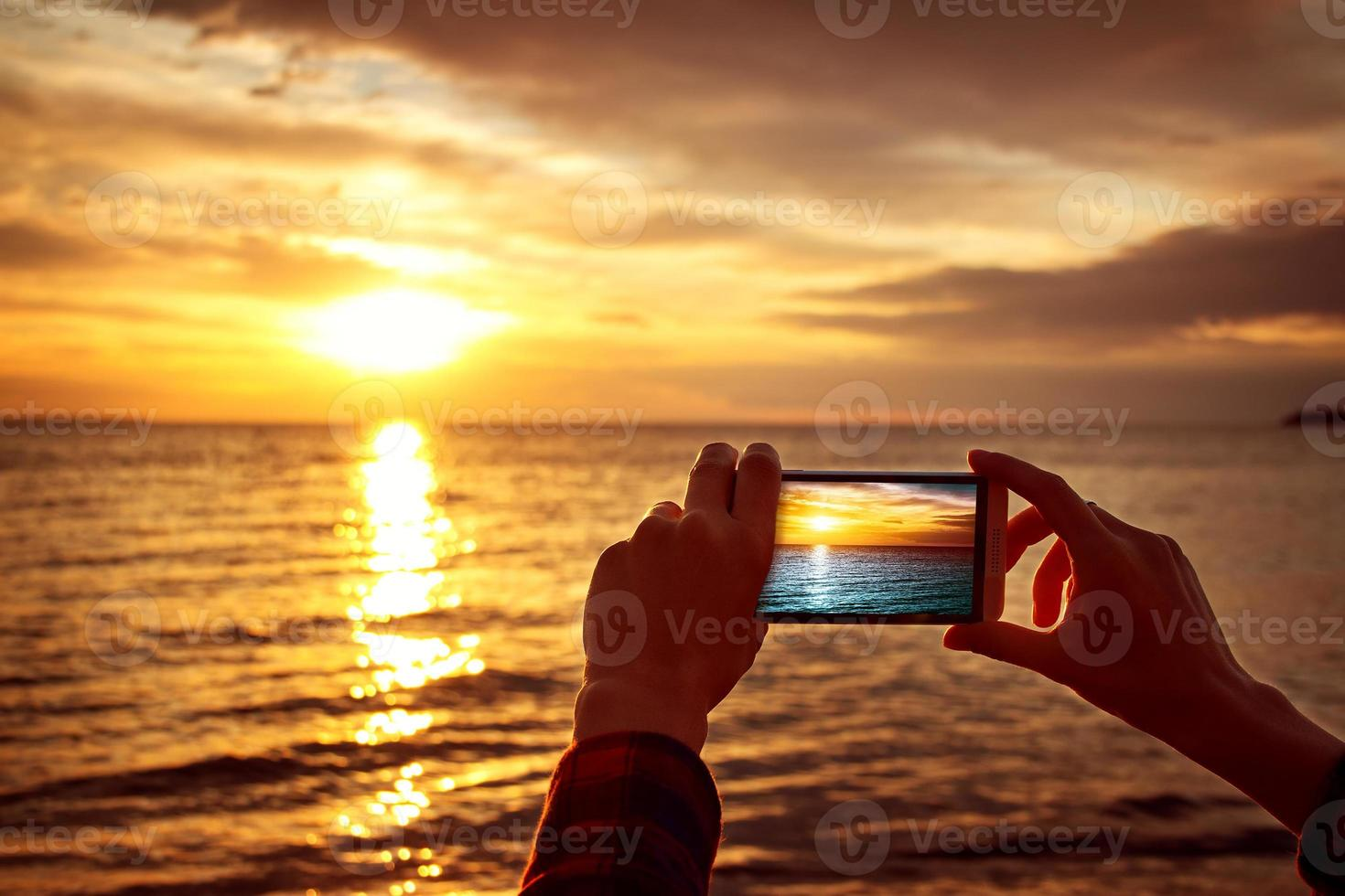 hands holding mobile phone at sunset photo