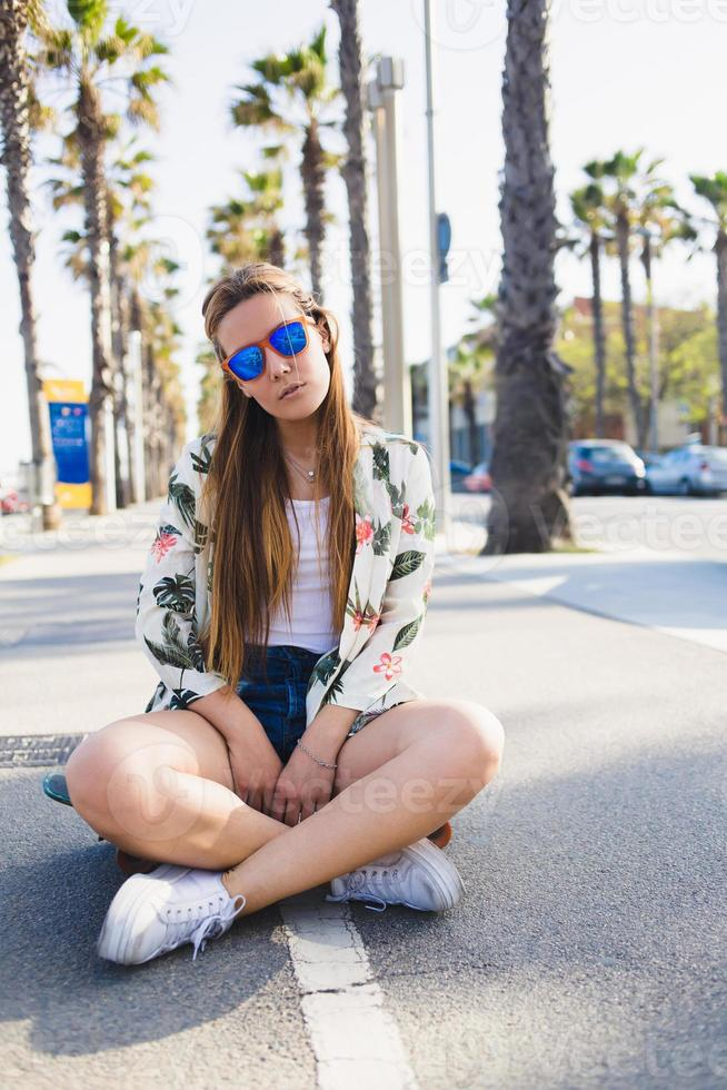 glamorosa joven skater relajante después de montar en penny board foto