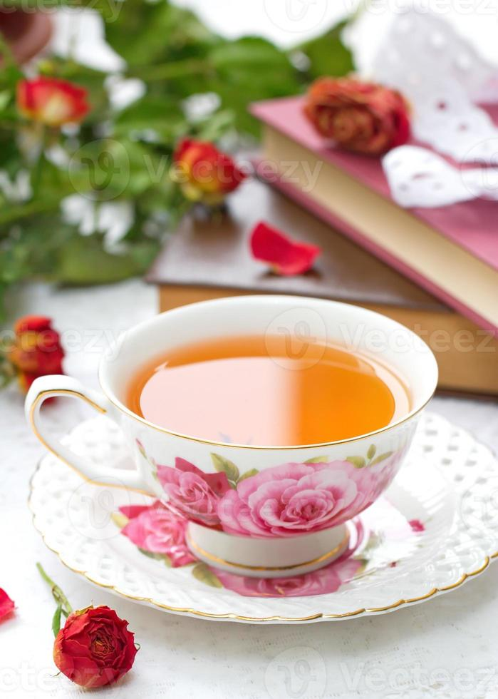 Still life with tea, books and roses photo