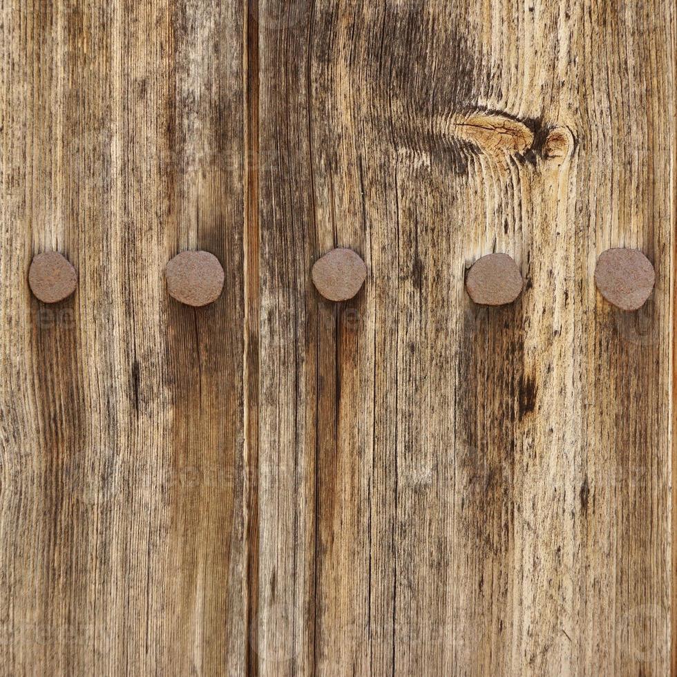 Panel de tablones de madera vieja con textura de clavos de hierro oxidado forjado foto