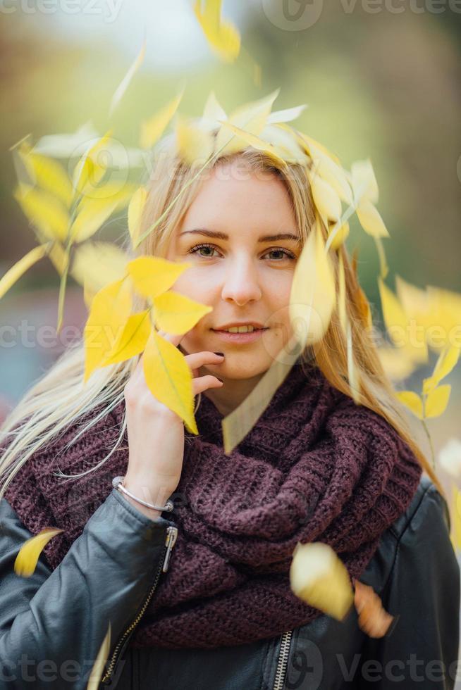 mujer joven con hojas de otoño en la cabeza. foto