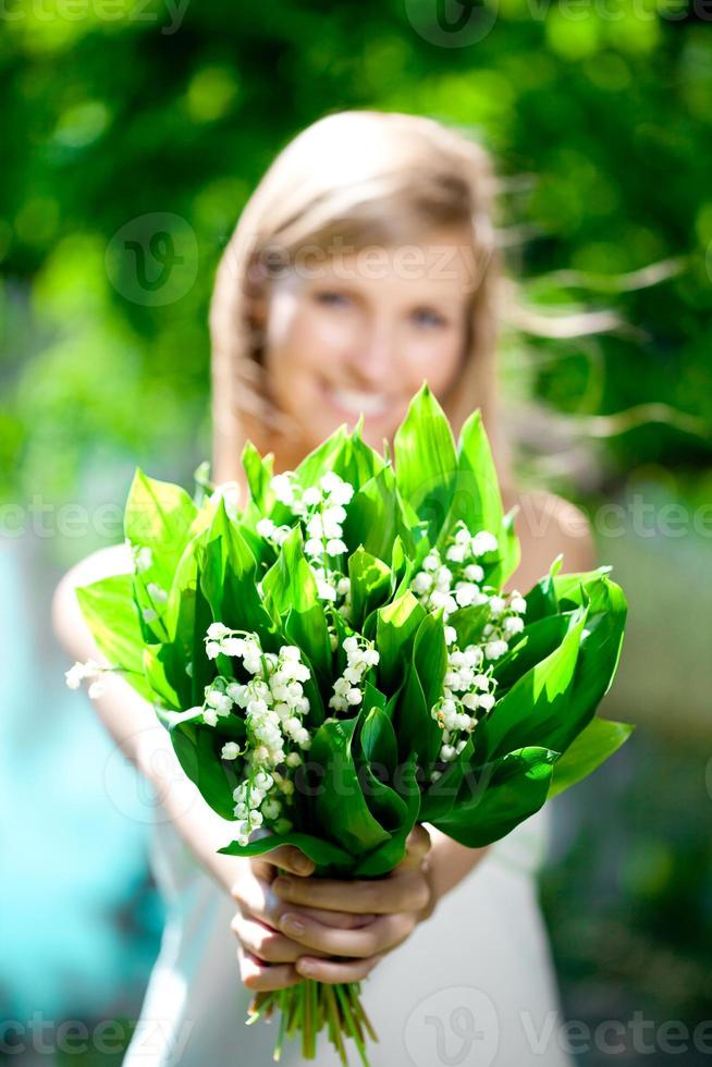 Young woman smiling and give a bouquet of flowers photo