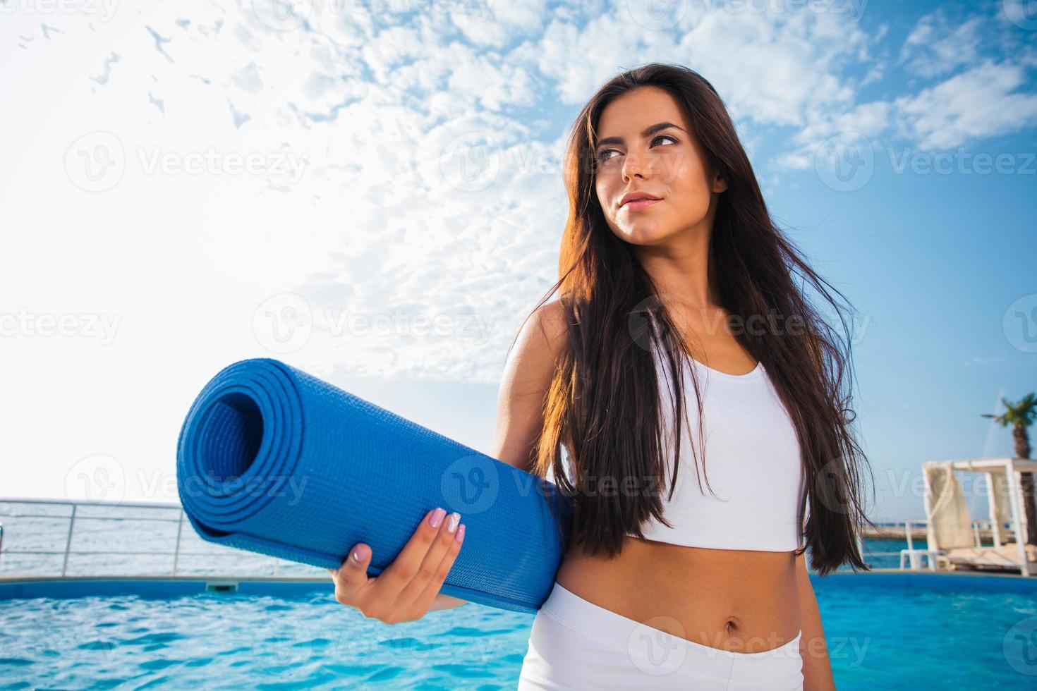 hermosa mujer sosteniendo estera de yoga foto