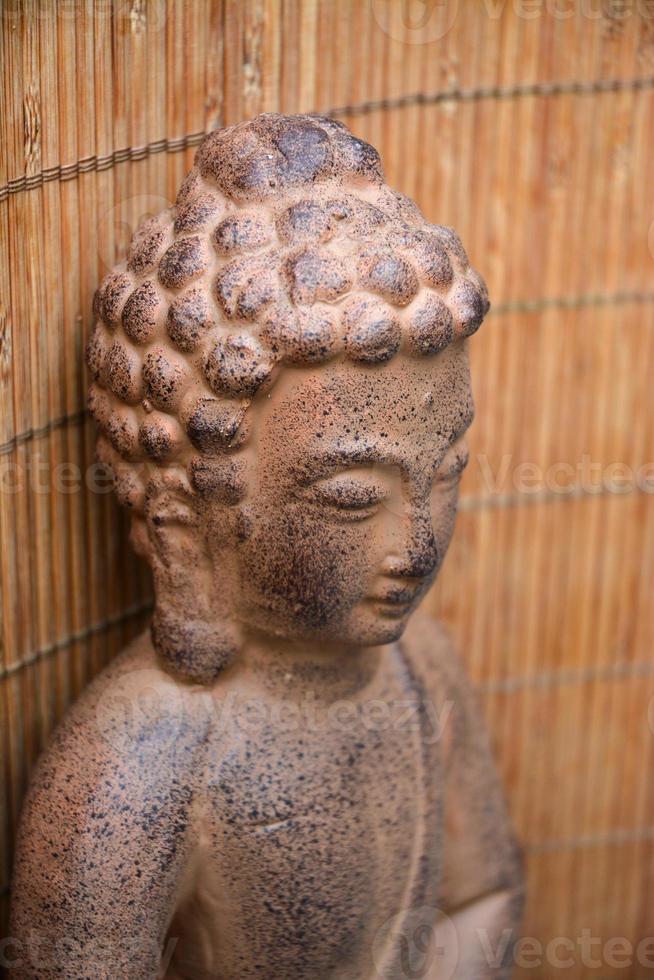 Retrato de la estatua de Buda marrón con fondo de bambú foto