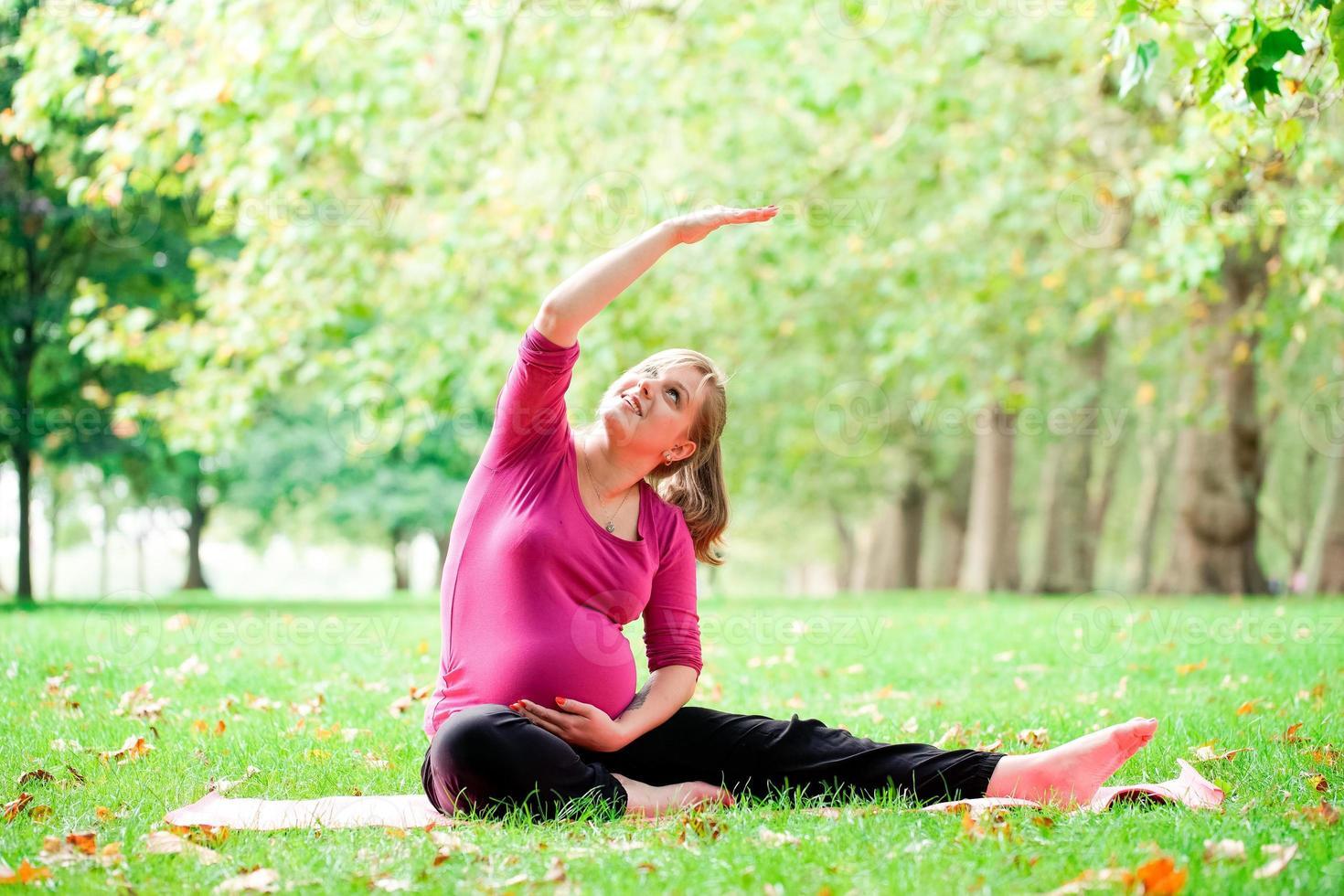 Mujer embarazada jugando yoga en el Hyde Park, Londres foto