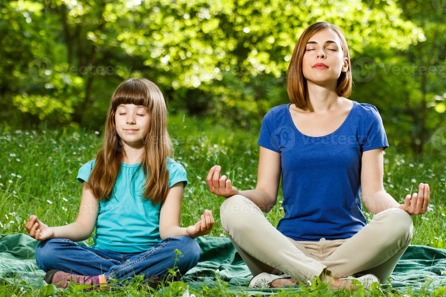 Mother and daughter meditating photo