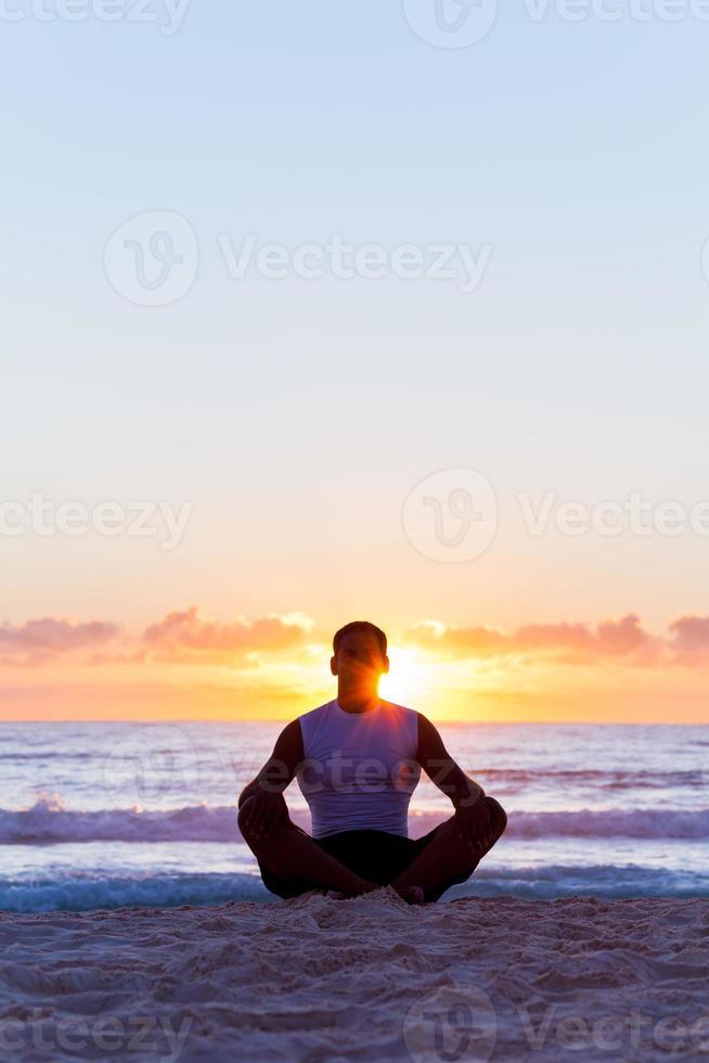 hombre meditando en la playa foto