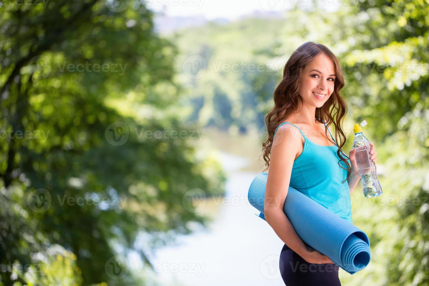 Cute woman with a yoga mat outdoors. photo