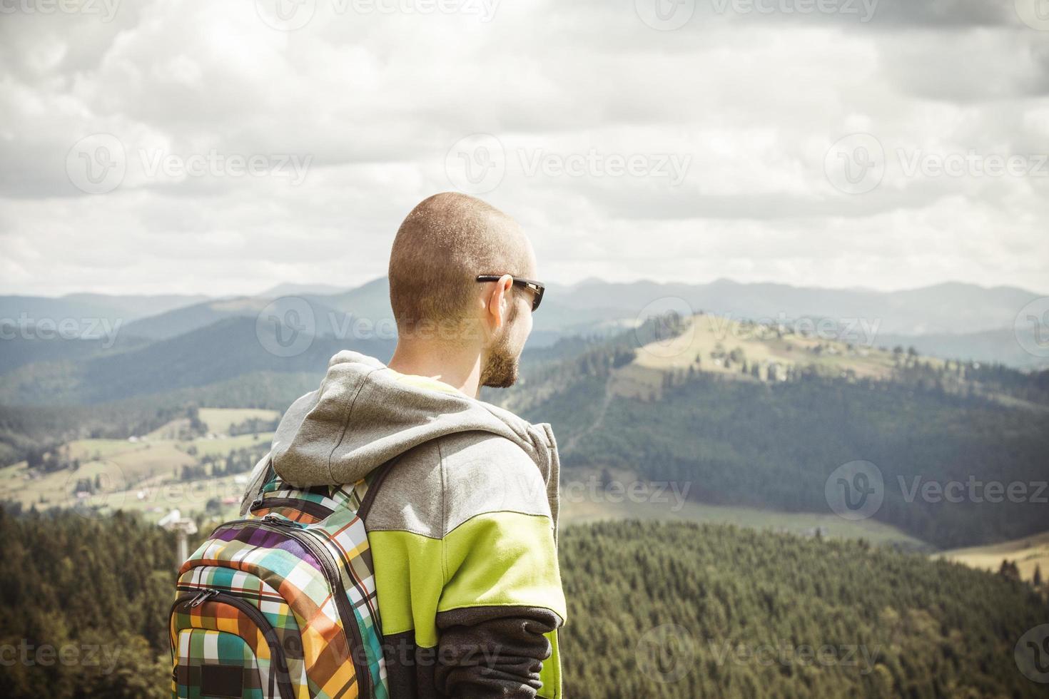 Man hiker enjoying mountain view photo